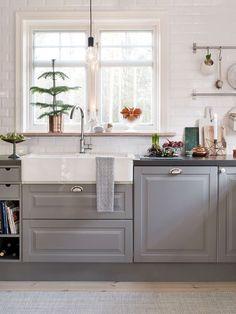 OMBONAD JUL I SKÄRGÅRDSHUSET: Köket har luckor i mjukt grått som ger en ombonad känsla. Fina skärbrädor finns nära till hands: grön marmor, H. Skjalm P, vit marmor, House Doctor, trä, Nicolas Vahé. Stjärnljusstake från Zelected by Houze. Granen har sobert pynt i vitt och guld, kulor från Åhléns och Granit | Lantliv