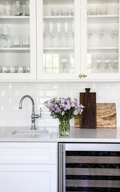 White glass front cabinets accented with brass vintage latch hardware are mounted above white shaker cabinets finished with a glass front wine fridge and a white quartz countertop fitted with a curved prep sink and a polished nickel gooseneck faucet fixed in front of white beveled subway backsplash tiles.