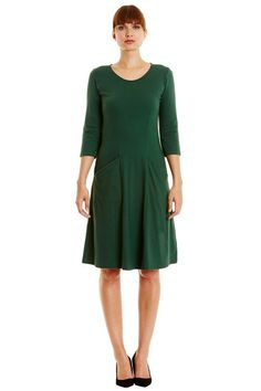 Dark green flared dress in 100% organic certified cotton. Below knee length with front pockets and long sleeves. Also available in burgundy. Length 103cm.