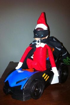Elf on the Shelf dresses up as Batman  Another great reader submission.  The reader commented: Our elf took the boys' Batmobile for a spin last night! He used a black bandana to make himself a Batman costume. My boys thought this was awesome!