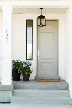 This entry and front door are so classy. Putty colored front door, white exterior and black assents on porch light, planters and window trim.