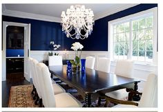 Peacock blue walls, dark wood table, upholstered chairs.  Conan O'Brien's dining room via Emily A. Clark.