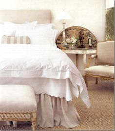 Love the comfortable, inviting bed dressed in neutral color linens, the seagrass rug, the french armchair and beautiful side table. Very calming effect.