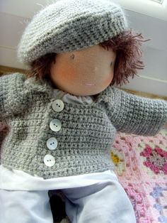 "Crocheted Doll Clothes Idea: Waldorf-style doll in gray beret and shell-buttoned cardigan on the French doll art appreciation blog, Raconte-moi une Poupée (23 Jul. 2011). Photo from blog contributor, ""poupeedoudou."""