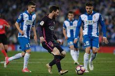 Barcelona's Argentinian forward Lionel Messi  (C) controls the ball past Espanol's midfielder David Lopez (R) during the Spanish league football match RCD Espanyol vs FC Barcelona atthe Cornella-El Prat stadium in Cornella de Llobregat on April 29, 2017. / AFP PHOTO / PAU BARRENA