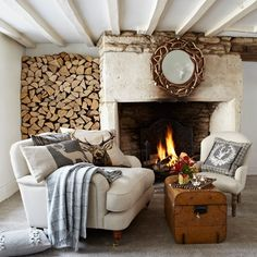 Cosy fireplace made more appealing by snuggler armchair and wall of firewood - from Country Living and Interiors Magazine. Found via housetohome.co.uk