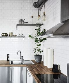 white subway tile backsplash all the way up to the ceiling with gray shelves and butcher block countertop.