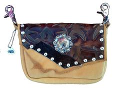WESTWARD BOUND CONCEALED CARRY - soft tan cowhide bag has dark brown hair-on-hide & a bold printed leather pattern. Centerpiece is silver & gold color concho w/ criss-crossed six-shooters. Etched silver studs add embellishment to flap. Fits .22 caliber, .38 special or small semi-automatic, iPhone 6 Plus & all large phones. Wear bag clipped to belt loops for hands-free carrying of your essentials. Interior includes a leather strap. Add the strap when you want a completely different look.