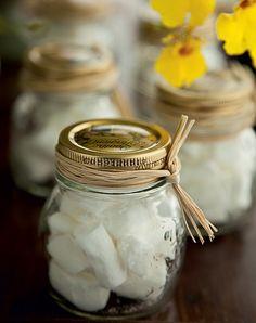 Para adoçar a despedida depois da festa, potinhos recheados com balas de coco e decorados com tiras de palha