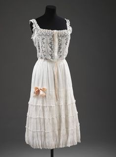 Unknown designer 1905 petticoat England, Great Britain. White lawn with lace insertions. It has pink ribbons threaded through the neck, armholes and waist. A pink ribbon bow decorates the sides of the flaring skirt. The skirt also has a crinkle texture on the lawn. The bodice fastens in the front with lawn covered buttons. *vintage leavers*