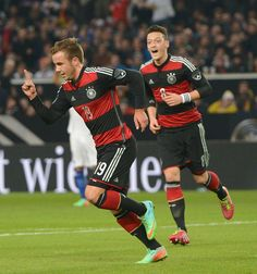 Germany's Mario Goetze , left, celebrates after he scored the opening goal while teammate Mesut Ozil, right looks on, during the friendly soccer match between Germany and Chile in Stuttgart, Germany, Wednesday March 5, 2014. (AP Photo/dpa,Bernd Weissbrod)
