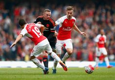 Wayne Rooney of Manchester United is tackled by Santi Cazorla and Aaron Ramsey of Arsenal during the Barclays Premier League match between Arsenal and Manchester United at Emirates Stadium on October 4, 2015 in London, England. (Oct. 3, 2015 - Source: Julian Finney/Getty Images Europe)