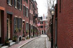 This is Acorn St on Beacon Hill in Boston. It is the oldest street in Boston and the most photographed sight. The street shows the progression from dirt to stone to cobblestone to brick. These were the homes of servants in the 1800s, now a tiny unit is worth millions. The gaslights are real and are lit 24 hours a day -- in the old day, they had a lamplighter to light them at night and extinguish them in the day. The street is narrow, maybe 1 car wide, but was typical of the streets in those…