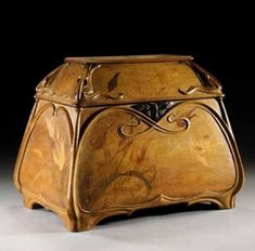 Emile Galle - Walnut and Marquetry Inlaid Casket, circa 1900. Signed with inlaid signature Gallé. Inlaid with tulips and with applied carved whiplashes framing each side, the hinged cover carved with foliate motifs to each corner and enclosing a void interior, the bronze escutcheon cast as a moth. H: 28cm, W: 36cm, D: 24cm. Sold at GBP 9360 in Sep 2003, Sotheby's.