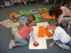 Kindergarteners sponge designs onto a giant alphabet.