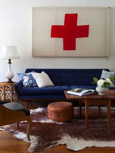 Eclectic living room design with blue velvet mid-century modern sofa, vintage cocktail table, white & brown cowhide rug, leather pouf, white lamp and art.
