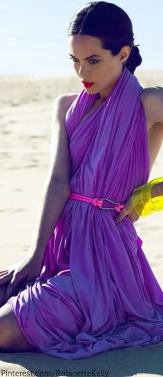 .Gorgeous sun kissed brunette in deep purple halter dress with pink belt and yellow bangles.