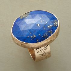 "Pyrite flecks make each deep blue lapis absolutely one of a kind. Jes MaHarry sets the faceted stone in 14kt gold, etching the outside of the band with flowers, the inside with ""let your love grow."" Exclusive. Handmade in USA. Whole sizes 5 to 9."