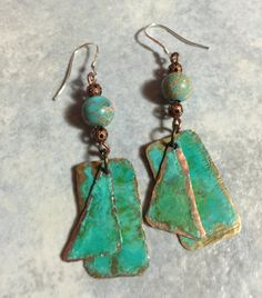 These earrings are made with sterling silver ear wires. They are oxidized copper with a green patina and a hammered texture and a turquoise