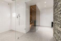 Väggar i vitt kakel med glansig yta och golv i grå klinker. En vägg i det stora badrummet täcks av natursten och förstärker spakänslan. Duschen är snarare ett duschrum, med en vägg i glas och en väldig takdusch. Också den stora bastun har en vägg helt i glas. I en avskild del av badrummet finns en vägghängd toalett och ett vägghängt handfat med en underdel i ljust trä. Basement Toilet, Divider, Bathtub, Bathroom, Furniture, Design, Home Decor, Dekoration, Standing Bath