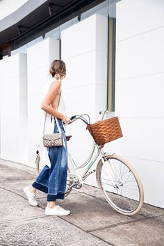Browse these blogger-approved ways to pose with a bicycle at @Stylecaster | 'The Chronicles of Her' in slouchy denim, white blouse and sneakers