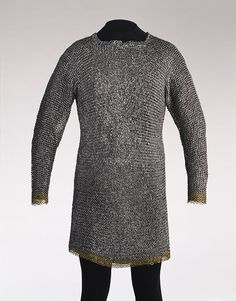 This mail shirt is rare in being well preserved and having two brass rings at the neck, each struck with an inscription, which is probably the name of its maker (BECHLER).    It is constructed from riveted steel rings, while the wrists and lower edge are decorated with borders of riveted brass rings. Although mail offered protection against the cutting edges of sword and battleaxe, it also required an underlayer of quilted fabric, both to make it more comfortable and to protect against the…