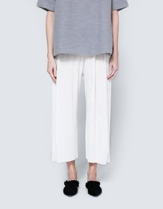 Trousers from House of Sunny in Ivory. Mini accordion pleat fabric. Pull on design. Elastic waistline. Dropped crotch. Straight leg. Unlined. Casual fit.     • Pleated sateen  • 100% polyester  • Dry clean