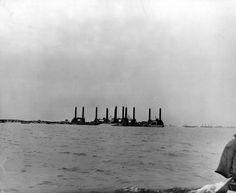 """Dans la rade de protection des navires (en arrière plan des caissons Phoenix) une énorme plate-forme dans le port artificiel Mulberry A d'Omaha Beach. Trois quais flottants """"Lobnitz"""" sont assemblés en forme de T et raccordés à une passerelle flottante """"Whale"""" qui les relie à la côte. Chaque quai Lobnitz coulisse verticalement le long de 4 grands pylônes fixes et posés sur le fond. Ce système est installé en face de Vierville-sur-Mer, à environ 1 km de la laisse de haute mer."""