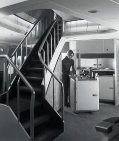 In 1970 a stewardess is seen preparing drinks in the upper-deck cocktail lounge of a Boeing 747 in a striped turtleneck and black slacks.