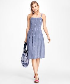 """<a href=""""#pdplearnmore"""" class=""""lm"""">The Red Fleece Collection</a><br>A new take on the classic shirtdress, this adorable 100% cotton poplin dress features a classic gingham pattern with a front button closure and two buttons at each strap for an adjustable fit.<br><br>31"""" center back length; machine wash; imported."""