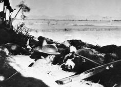 An American soldier stands tense in his foxhole on Bataan peninsula, in the Philippines, waiting to hurl a flaming bottle bomb at an oncoming Japanese tank, in April of 1942. (AP Photo)