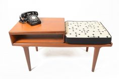 "Crafted by Younger of England, this mid century modern telephone bench is crafted in teak and floats on sculpted legs.  Perfect for any entryway, this time capsule piece wears its newly reupholstered Eames Dot Print fabric!  Phone book storage is perfect for any of your ""modern"" storage needs. In excellent original condition with typical wear for its vintage. Measures: 42″ long x 18″ wide x 21.5″ tall Seat: 18.5″ wide x 18″ deep x 19.5″ tall $1150.00"
