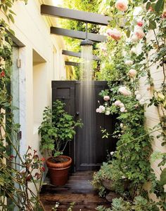 Consider this an outdoor oasis at its best. An overhead shower installation is only closely rivaled by the abundance of garden roses and vibrant greens.