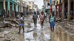 People walking down a flooded street in the town of Jeremie, Haiti on 6 October 2016