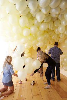 Tape balloon strings at various heights to make a balloon wall!