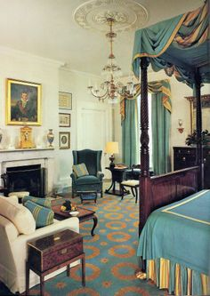 Roper House, Charleston, South Carolina - In the master bedroom a portrait from the school of 18th-century French artist Jacques-Louis David is displayed above a mantel exhibiting a late Empire clock & a pair of Old Paris urns. The blue-&-gold fabrics that adorn the Federal bed repeat the tones of the custom carpet. Photo by Van Jones Martin