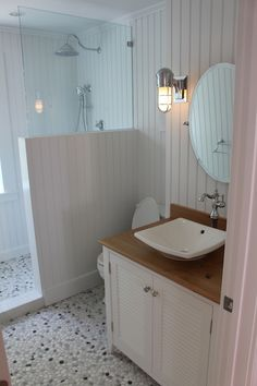 The first floor bath has Nantucket beadboard made of PVC wrapping all the way into the shower and a sheet of glass, half milky half clear that swings over the window for privacy and to keep water out but lets the light in.