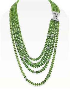 A PERIDOT AND DIAMOND NECKLACE  Comprising five strands of faceted peridot beads, accented at one side with circular-cut diamond spacers, joined by a circular-cut diamond clasp, mounted in 18k white gold, 22½ ins.