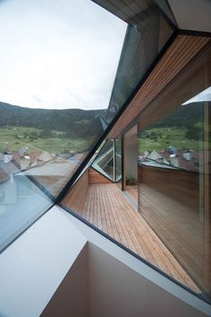 Apartments featuring shards of glazing that frame views of the distant mountains in Italy.