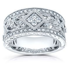 Diamond anniversary ring in fourteen karat white gold with vintage floral decorations and milgrain edging.