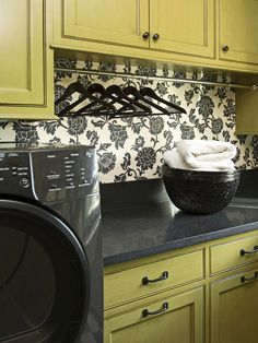 Eye-Catching Patterns          Striking wallpaper instantly defines a space, while looking trendy and playful. Choose a pattern that matches your color scheme for an effortless way to accent your laundry room's decor. A cream and black floral design keeps with the dark hardware and appliances and pops against the green painted cabinetry.