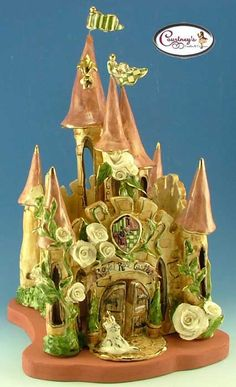 """The Royal Rose Castle is an amazing creation by Heather Goldminc for her  Clayworks Studio Originals Collection.The Royal Rose Castle features a gold fleur-de-lis on the highest turret and a cat with a golden crown by the front gate.  The Castle is covered in lovely roses and has a coat of arms over the gate.  The Castle's interior towers and exterior walls are attached to the rose colored base.The Royal Rose Castle is 16"""" tall by 10"""" square.This one was already snapped up ... but with a…"""