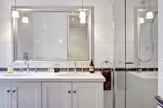 Mirror, lights and white cabinets