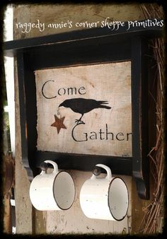 """Primitive Black Peg Shelf with Cups.. tea stained fabric... stenciled crow with rusty star.. simply reads """"Come Gather""""."""