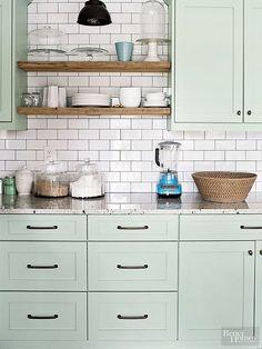 Light Green Painted Kitchen Cabinets with Shiny White Subway Tile Backsplash.