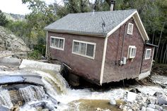 WATER DAMAGE: Water flowed past a damaged home in Salina, Colo., Tuesday, after heavy flooding in the state. (Jeremy Papasso/Daily Camera/As...