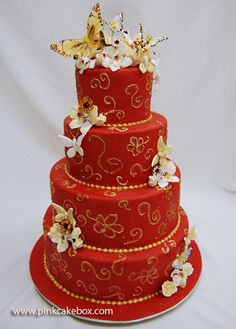 Red wedding cake with gold designs and colorful flowers