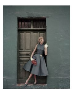 Model in blue-grey Irish linen afternoon dress with gold medallion attached to the belt, by Heatherlane, 'Vogue' magazine, May 1955. Silk purse by MM, shoes by Pappagallo. Photo by Leombruno-Bodi.