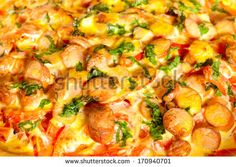 Detail of pizza with potatoes, tomatoes and wurst.