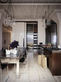 Reclaimed wood on the floors and ceilings  compliment the salvaged lighting fixtures. Put next to the clean modern design of the kitchen creates the perfect natural contrast